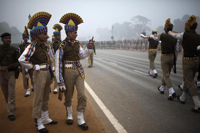 An Indian soldier takes pictures with a mobile phone of comrades marching during rehearsal for Republic Day parade amid fog on cold winter morning in New Delhi