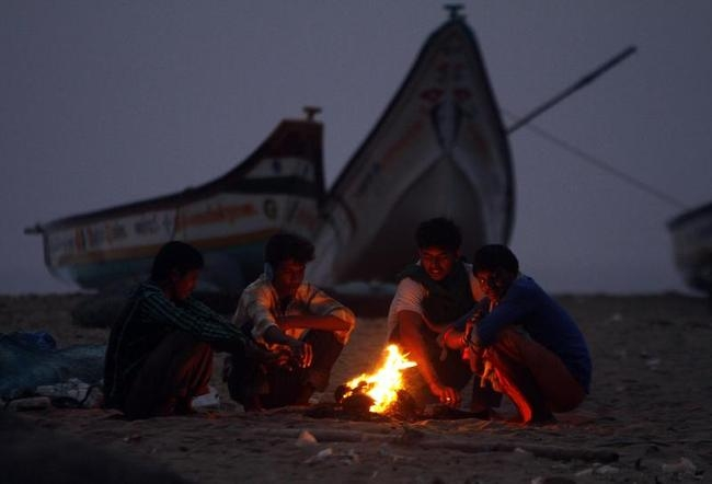 Fishermen warm themselves by a fire near their fishing boats before venturing into the sea on a cold morning in Chennai