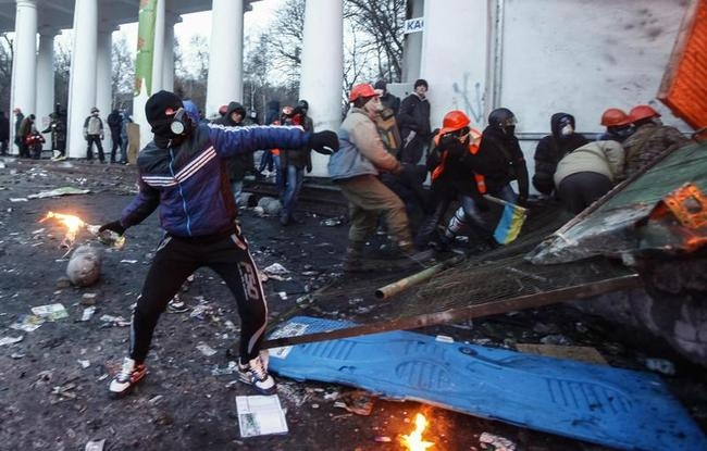 A pro-European integration protester throws a Molotov cocktail towards riot police during clashes in Kiev