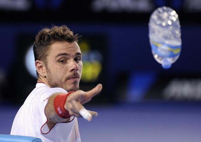 Stanislas Wawrinka of Switzerland throws an empty bottle to rubbish bin during a break