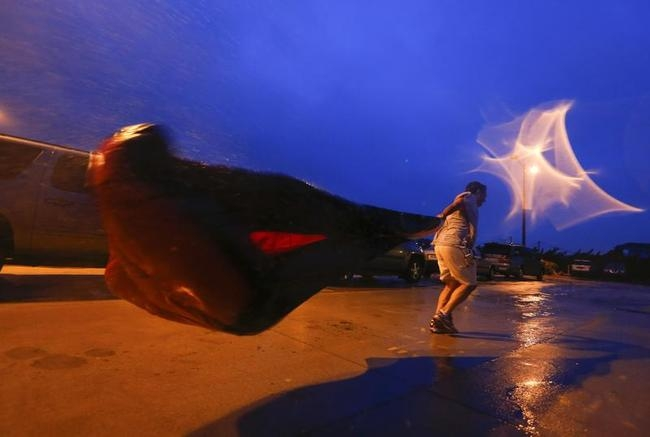 Carter Cromley of Virginia carries the cover for his jet ski that was blown off as hurricane Arthur continues in Nags Head