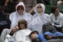 Spectators try to keep dry as rain stops play on Court Three at the Wimbledon Tennis Championships, in London