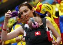A fan of Switzerland carrying a child, takes a photo before their 2014 World Cup Group E soccer match against Ecuador at the Brasilia national stadium in Brasilia