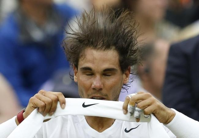 Rafael Nadal of Spain throws his head back as he changes his headband during his men