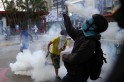 Anti-government protester throws a gas canister back at the police during riots at Altamira square in Caracas