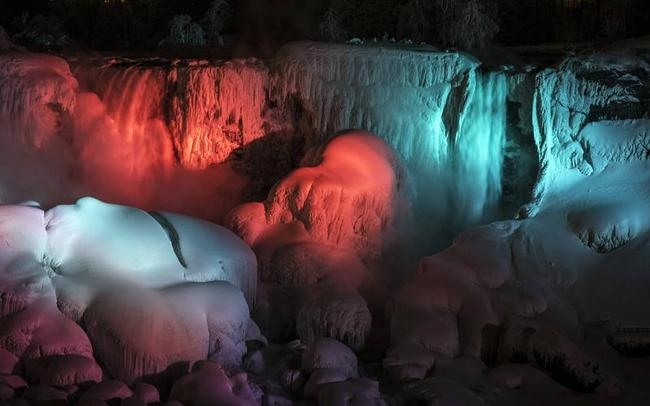 A partially frozen American Falls is seen lit by lights during sub freezing temperatures in Niagara Falls