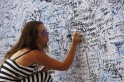 A woman writes on a wall dedicated to the passengers of the missing Malaysia Airlines flight MH370 before the Malaysian F1 Grand Prix at Sepang International Circuit outside Kuala Lumpur
