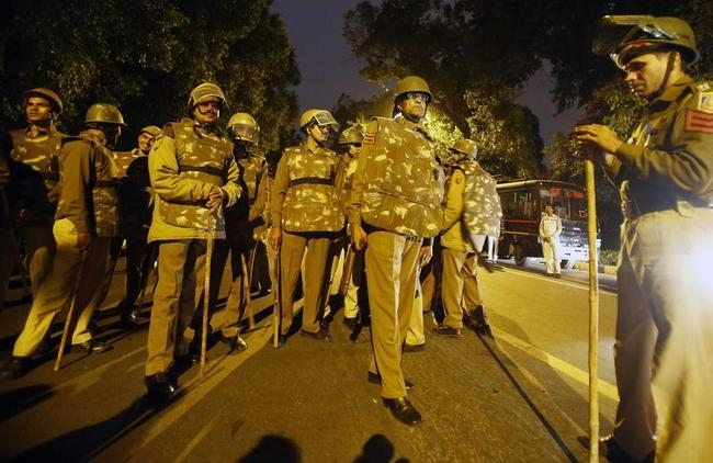 Indian policemen stand guard outside the headquarters of BJP during a protest by the supporters of AAP in New Delhi
