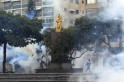 An anti-government protester walks amidst teargas during clashes with police at Altamira square in Caracas