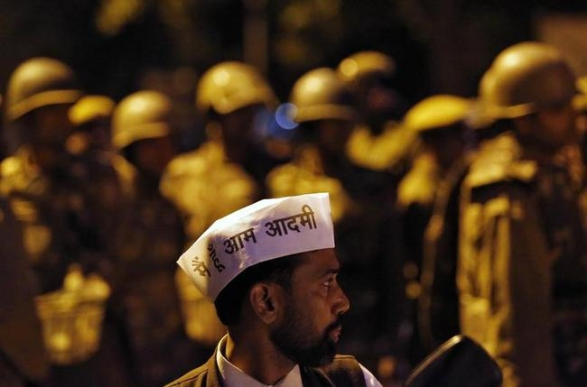 A supporter of AAP stands in front of Indian policemen on guard during a protest outside the headquarters of BJP in New Delhi