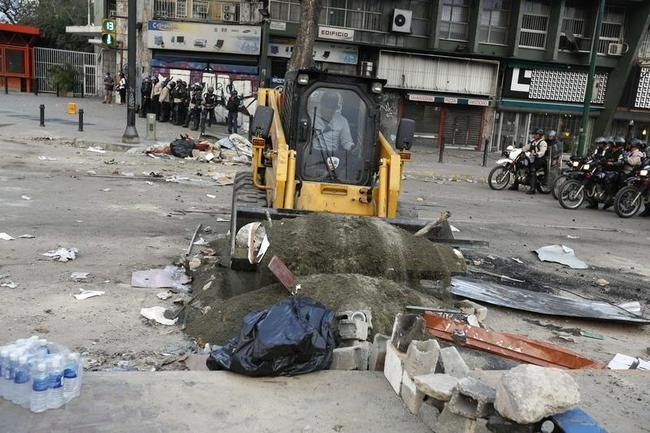A barricade set by anti-government protesters is removed at Altamira square in Caracas