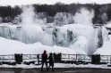 A couple looks out over partially frozen American side of Niagara Falls during sub-freezing temperatures in Niagara Falls
