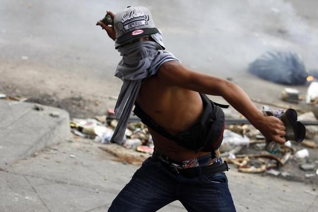 An anti-government protester throws stones at police during riots at Altamira square in Caracas