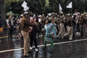 Supporters of AAP argue with an Indian policeman during a protest outside the headquarters of BJP in New Delhi