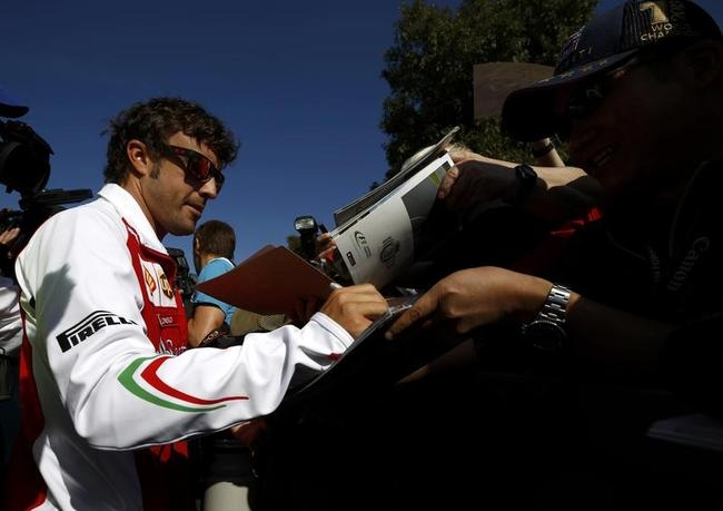 Ferrari Formula One driver Alonso of Spain signs autogaphs during the first practice session of the Australian F1 Grand Prix in Melbourne