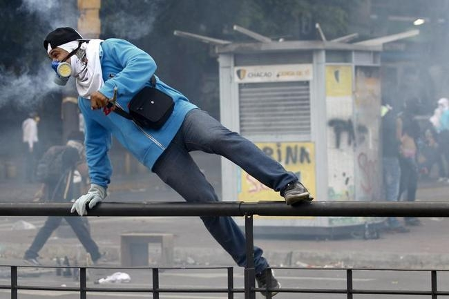 An anti-government protester jumps a fence during riots at Altamira square in Caracas