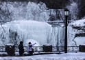 People look out over partially frozen American side of Niagara Falls on during sub-freezing temperatures in Niagara Falls